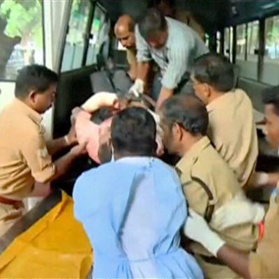 Loukkaantunutta autetaan ambulanssista sairaalaan.