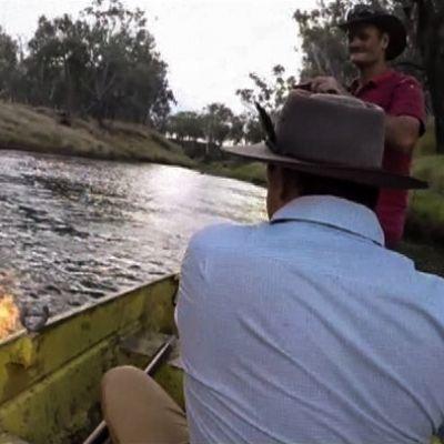 kaksi miestä veneessä ja liekki joessa