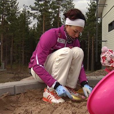 Mona-Liisa Malvalehto hiekkalaatikolla tyttärensä kanssa.