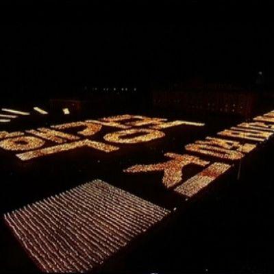 Laaja kuva aukiolla pimeässä illassa marssivista soihtua kantavista esiintyjistä.
