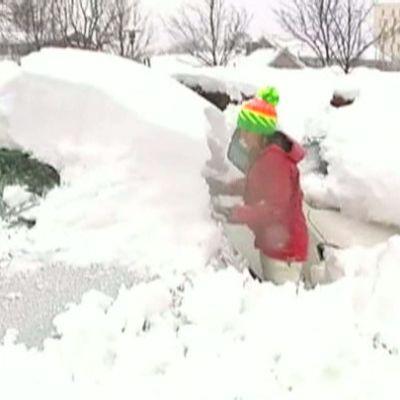 Tyttö tai nainen kaivaa autoa esiin noin puolen metrin lumikerroksen alta.