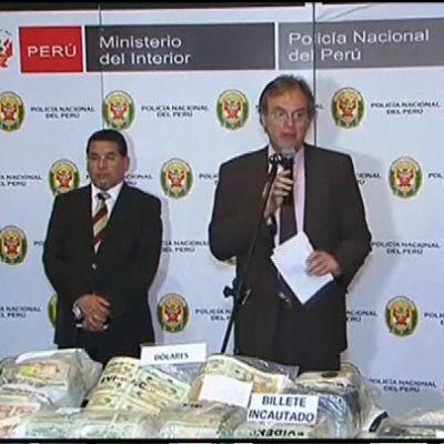 Perun sisäministeri Carlos Basombrio puhumassa tiedotustilaisuudessa ennätystakavarikosta. Kuvan etualalla on väärennettyä rahaa.