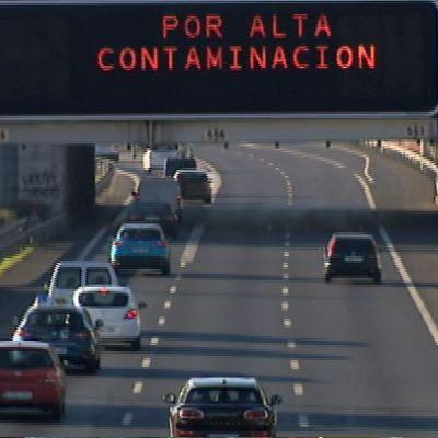 Kuvassa autoja ja valotaulu, joissa muistutetaan saasteista.
