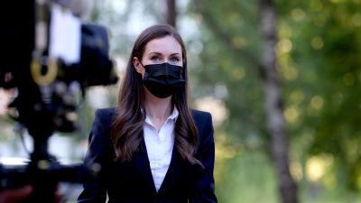 Sanna Marin anländer till Yles studiohus. Framför henne står en filmkamera.