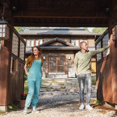 Nainen ja mies seisovat japanilaistyylisellä portilla, taustalla näkyy piha ja talo.