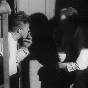 Metsätyömiehet rentoutuvat tupakan äärellä savottamajassa 1966.
