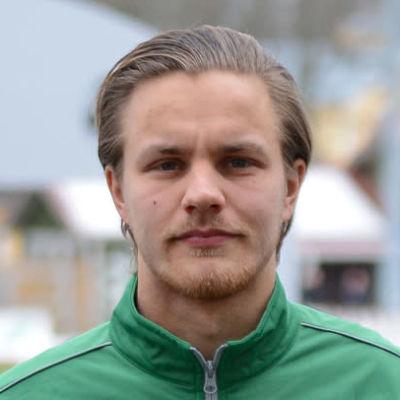 En man i grön jacka står framför en fotbollsplan.
