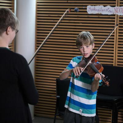 Vasemmalla opettaja ja oikealla näppäripelimanni soittamassa viulua.