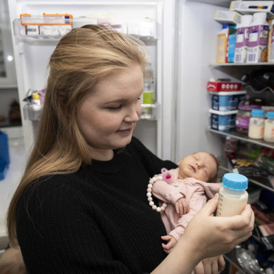Nainen pitelee sylissään lasta avoimen jääkaapin edessä. Toisessa kädessään hänellä on maitopullo.