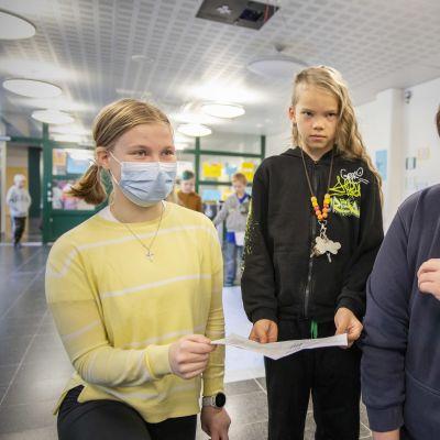 Pataluodon koulun 4.-luokkalainen Väinö Lahtinen näyttää hyvien tekojen passiaan 9.-luokkalaisille Erin Parkkiselle ja Mikko Nuutiselle.