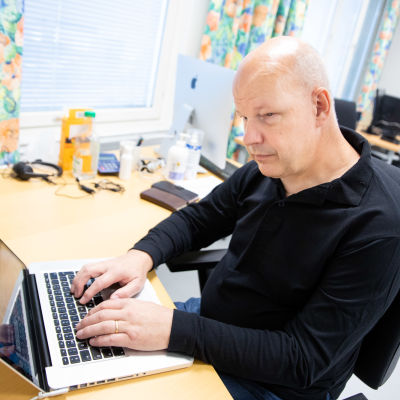 Hannu Suvanto käyttää kannettavaa tietokonetta Varsinais-Suomen näkövammaiset ry:n kerhotilassa Turussa.