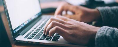 En person skriver på en laptop-dator