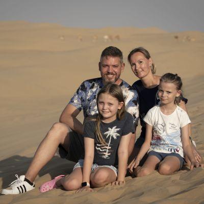 En kvinna och en man plus två barn sitter på sand i en öken.