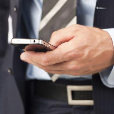 En man i kostym håller en telefon i sin hand