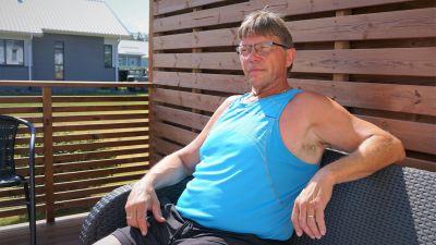 Man i blå ärmlös t-skjorta sitter på en terass.