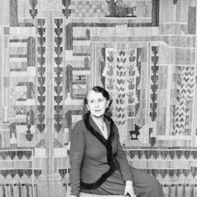 """Loja Saarinen på 1940-talet framför väggbonaden """"The Cranbrook Map""""."""