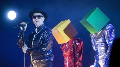 Pet Shop Boysin Neil Tennant ja laatikkopäitä lavalla.