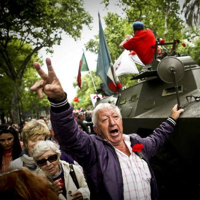 En man gör victorytecknet framför en av fordonen som hade använts i nejlikerevolutionen