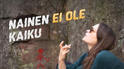 Teoskuvassa Salla Hämäläinen näyttää räppitunnusta sormillaan muinaisten kalliomaalausten edessä