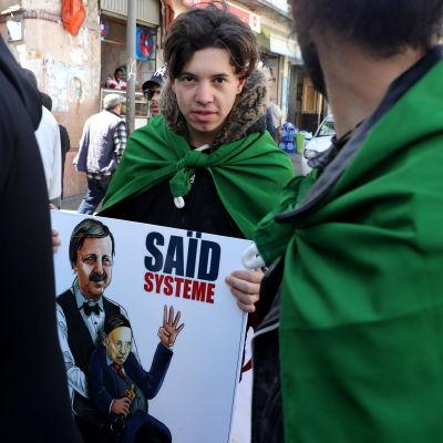 En man står med ett plakat i handen där Saïd Bouteflika ser ut att leda algeriets forna president