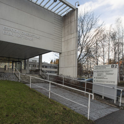 """En modern byggnad som det står """"Esbo rättshus"""" på. Huvuddörren och en trappa syns framför byggnaden."""
