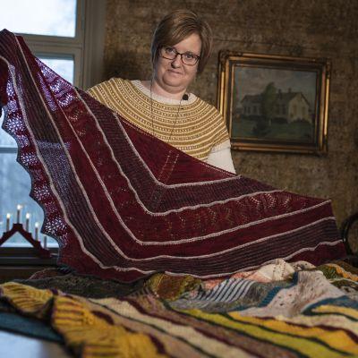 kvinna håller upp stickad sjal