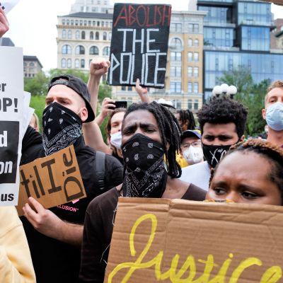Demonstranter som protesterar mot polisbrutalitet håller i skyltar och har munskydd på sig i USA.