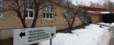 Pargas hälsocentral och ÅUCS psykiatriska avdelnings byggnad, en låg byggnad med gulbruna tegelstenar på väggen, med snö på marken.