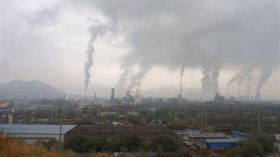 Skorstenar skjuter rök mot himlen vid fabriker i Lanzhou.