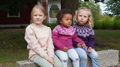 Lapset istuvat penkillä, strömsöpuserot lastenmallina päällä.
