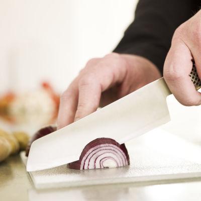 Kniv och lök på skärbräda.