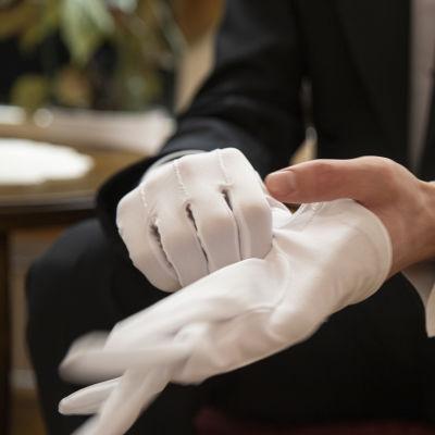 Mies laittamassa juhlapukuun kuuluvia hanskoja käteen.