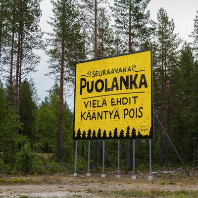 Suuri keltainen kyltti metsän laidassa, jossa lukee 'Puolanka, vielä ehdit kääntyä pois.'