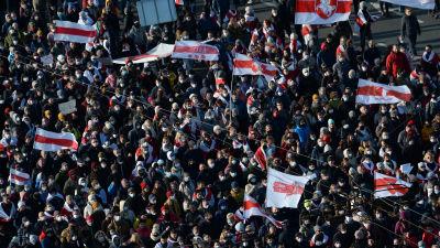 Demonstranter med vit-röda flaggor