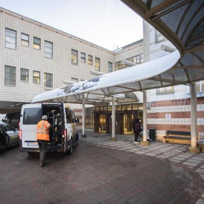 Ingången till ett sjukhus. Flera bilar står vid ingången och det ser ut som att patienter lastas ur dem.