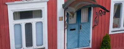 Närbild av ett rött trähus med vita fönsterlister och en blå dörr.