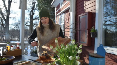 Nainen valmistaa ruokaa ulkona