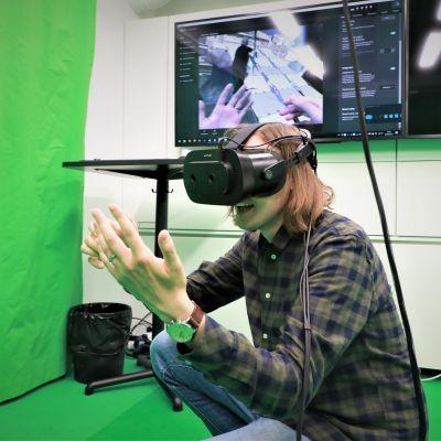 Toimittaja Hallamaa Varjo oy:n virtuaalimaisemassa, kädet avaruudessa