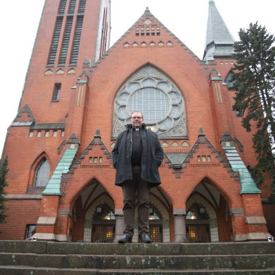 Pappi seisoo  kirkon edessä