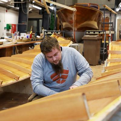 puuveneveistäjä Taneli Hakkarainen hio veneenlaidaksi tulevaa puuelementtiä