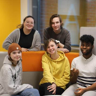 Elever vid Turun normaalikoulu sitter i en soffa med en grann gul vägg bakom.