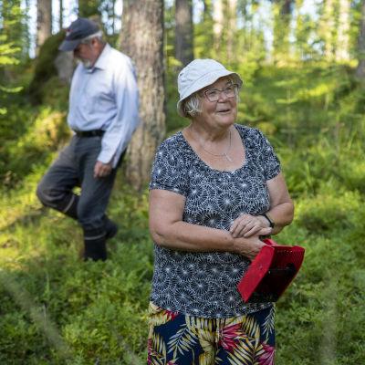 Hannele Viljakainen seisoo metsässä mustikanpoimuri kädessään, hänen miehensä kulkee taustalla etsien mustikoita