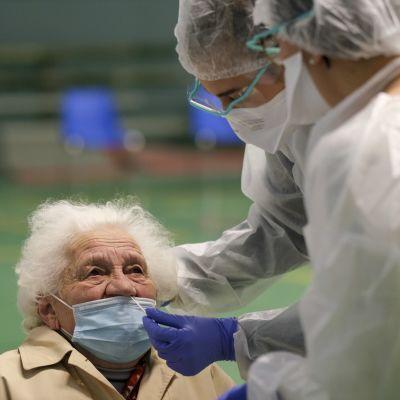 Vanha nainen saa nenäänsä testeipuikon kahdelta suojavarusteisiin pukeutuneelta henkilöltä.