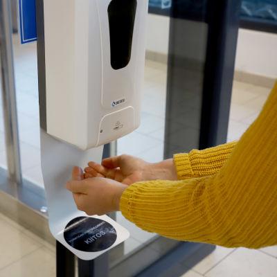 Två händer under en automat som doserar handsprit.