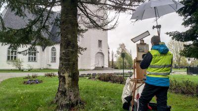 En konstnär står vid ett staffli och målar av en kyrka