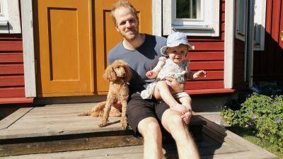 En yngre man sitter på en trappa och ler. Han har en liten flicka i famnen och en hund bredvid sig.