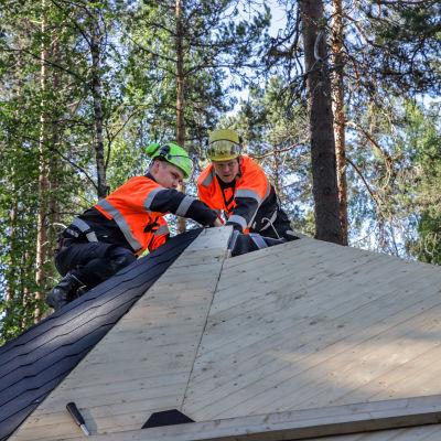 Rakennusmiehet Markus Parviainen ja Sami Laamanen kodan katolla.