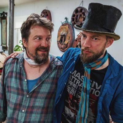Två män håller varann om axlarna i en konstnärsstudio, mannen till vänster har rutig flanellskjorta och skägg, mannen till höger bär sliten cylinderhatt, rutig tyghalsduk och blå skjorta, även han skäggig.