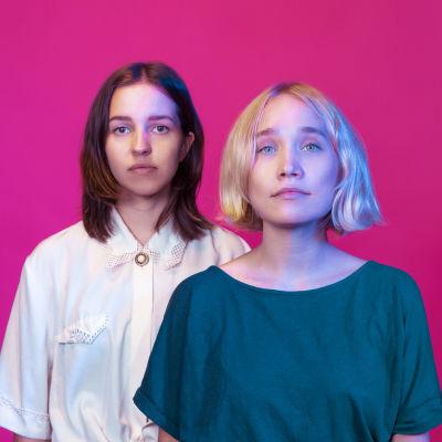 Ruskeahiuksinen ja vaaleahiuksinen nainen seisovat pinkin taustan edessä katsoen suoraan kameraan. Vihreään paitaan pukeutunut vaaleahiuksinen seisoo edempänä, valkoiseen, pitsikauluksiseen paitaan pukeutunut ruskeahiuksinen taaempana.