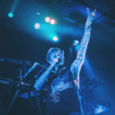 Rap-artisti Machine Gun Kelly seisoo lavalla mikki suunsa edessä ja käsi ilmassa sormet pirunsarvi-asennossa.